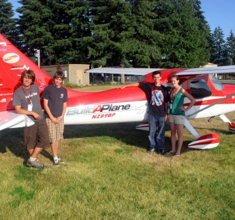 youth_eagles_in_front_of_red_plane-scaled.jpg